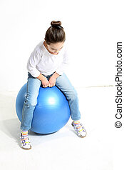 Little girl sitting on the ball