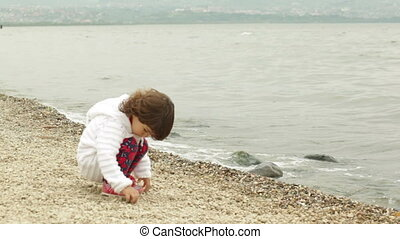 little girl sitting on the beach and throwing stones water
