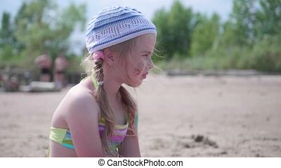 Little girl sitting on the beach, hot summer day. Carefully and thoughtfully looking into the distance.