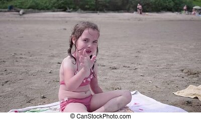 Little girl sitting on the beach, hot summer day. Waving and smiling