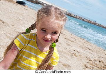 Little girl sitting on the beach