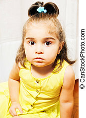 Little girl sitting on the floor closeup