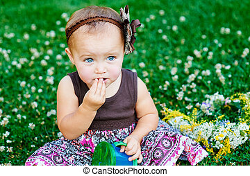 Little girl sitting on the grass and eats candy