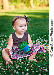 little girl sitting on the grass and eats cookies