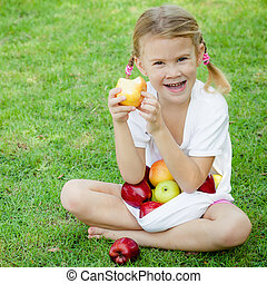 little girl sitting on the grass and holding apples