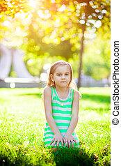 little girl sitting on the grass