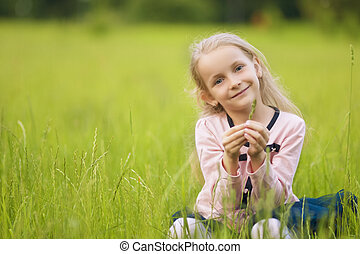 little girl sitting on the grass on lawn