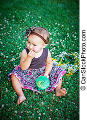 little girl sitting on the grass