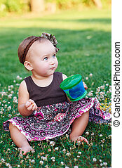 little girl sitting on the grass with a mug