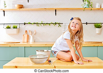 little girl sitting on the kitchen wooden table