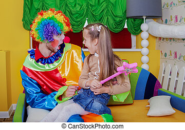 Little girl sitting on the lap of a cheerful clown