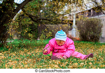 little girl sitting on the lawn in autumn