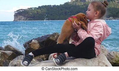 Little girl sitting on the rocks with her sweet puppy