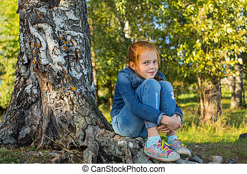 Little girl sitting on the roots