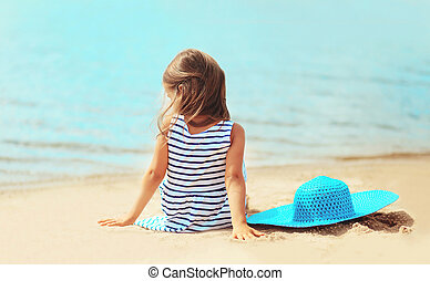 Little girl sitting on the sand beach with straw hat near sea in summer day