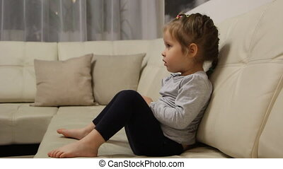 Little girl sitting on the sofa and watching tv