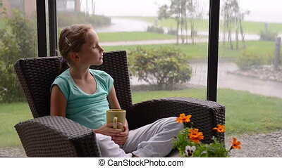 Little girl sitting on the sun lounge during the rain with cup of hot drink
