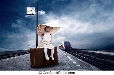 Little girl sitting on vintage baggage on the train platform...