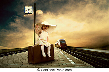 Little girl sitting on vintage baggage on the train platform...