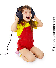 Little girl sitting on white with large earpieces
