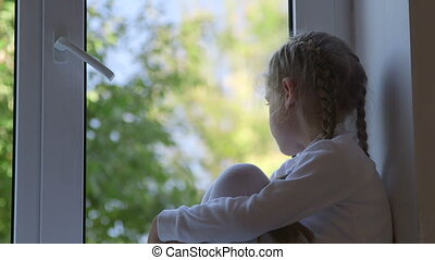 Little girl sitting on windowsill and looking out the window close-up