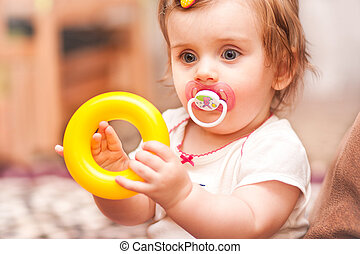 little girl sitting playing with a toy ring.