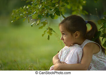 girl sitting under a tree