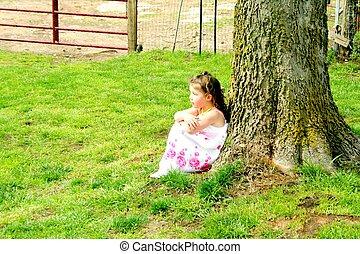 Little girl sitting under tree
