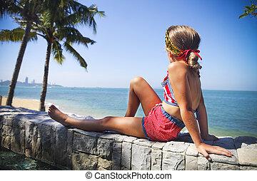 Little girl sitting underneath a palm at the tropical beach