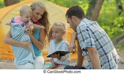 Little girl sitting with a tablet on a picnic with her wonderful family