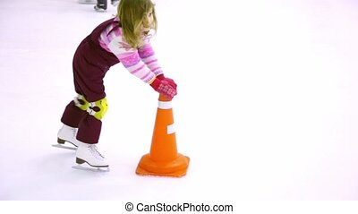 Little girl skates on ice rink helps herself by holding props