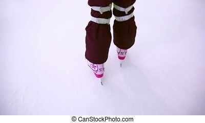 Little girl skates on ice rink, only legs are visible
