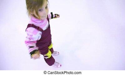 Little girl skates on ice towards the edge of rink