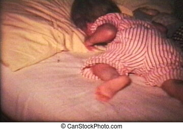 A little girl tosses and turns trying to sleep in her bed. (Scan from archival 8mm film)