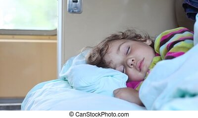 little girl sleeping in compartment of moving railway carriage