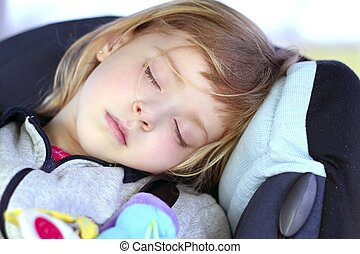 little girl sleeping on children car safety seat belt happy...