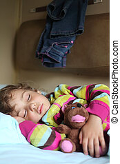 little girl sleeps in train with puppet