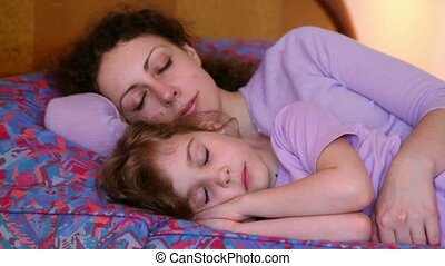 Little girl sleeps with hands under head near mother