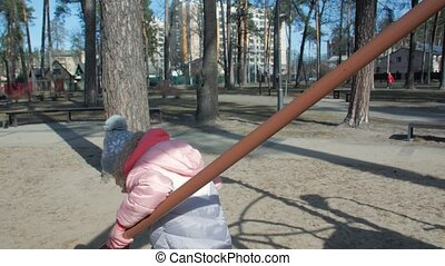 Little girl sliding on playground in the park