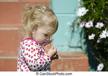 Little girl smell flower