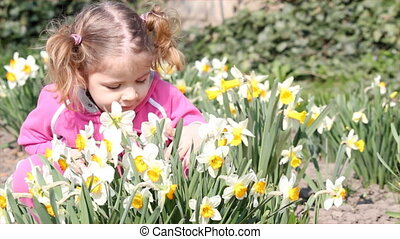 little girl smell flowers