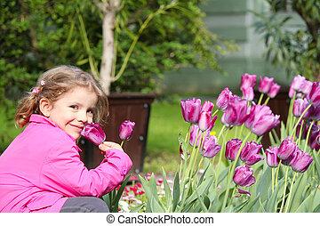 little girl smell tulip flower