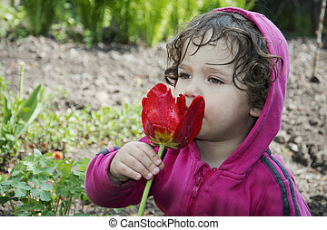 Little girl smelling a spring tulip.
