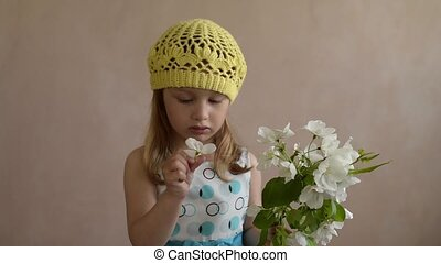 Little girl smelling an apple flower