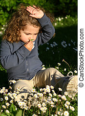 little girl smelling the daisies