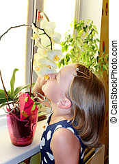 little girl smells orchid in the room