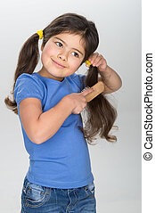 little girl smiling and combing hair. pretty girl wearing jeans and blue t-shirt