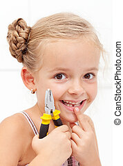 Little girl smiling holding her missing tooth with pliers -...