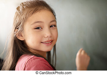 little girl smiling in front of chalkboard
