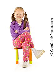 Smiling little girl sitting on a small chair